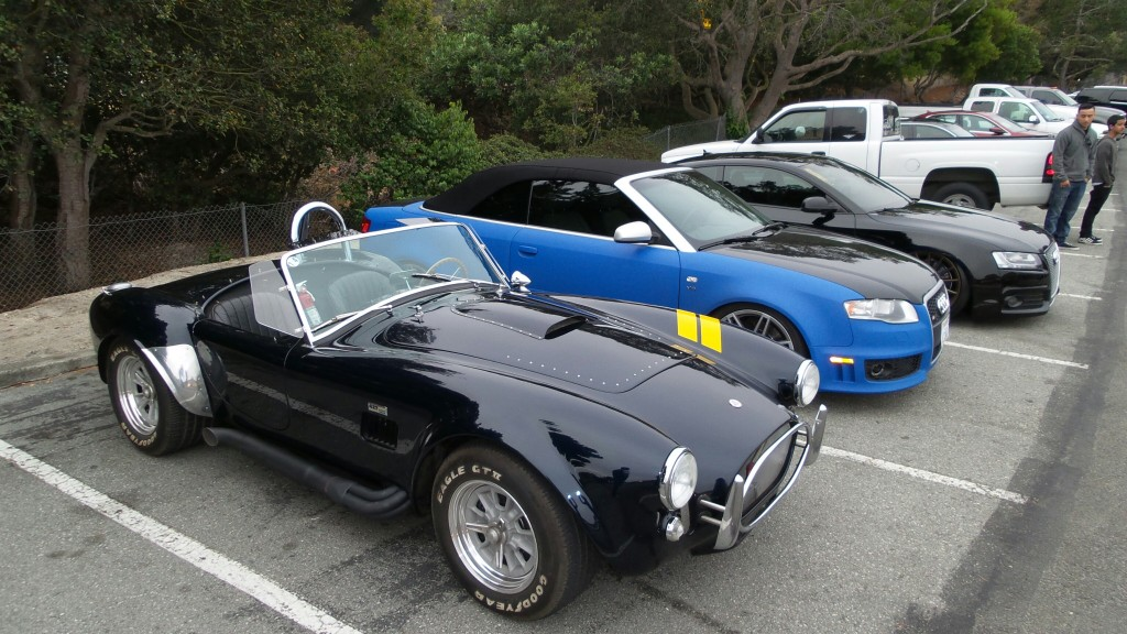 A lesson in contrast: A simple and brutish Cobra is parked alongside two heavily customized, high tech Audis.