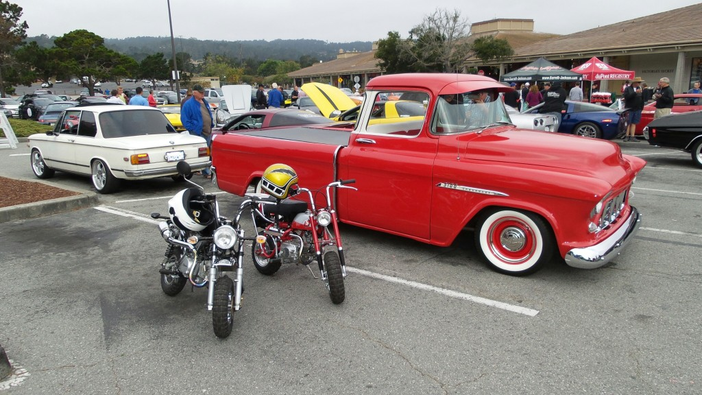 A pair of retro Honda Trail 50 mini-bikes are hanging out next to a nicely lowered Chevy 3100 pickup.