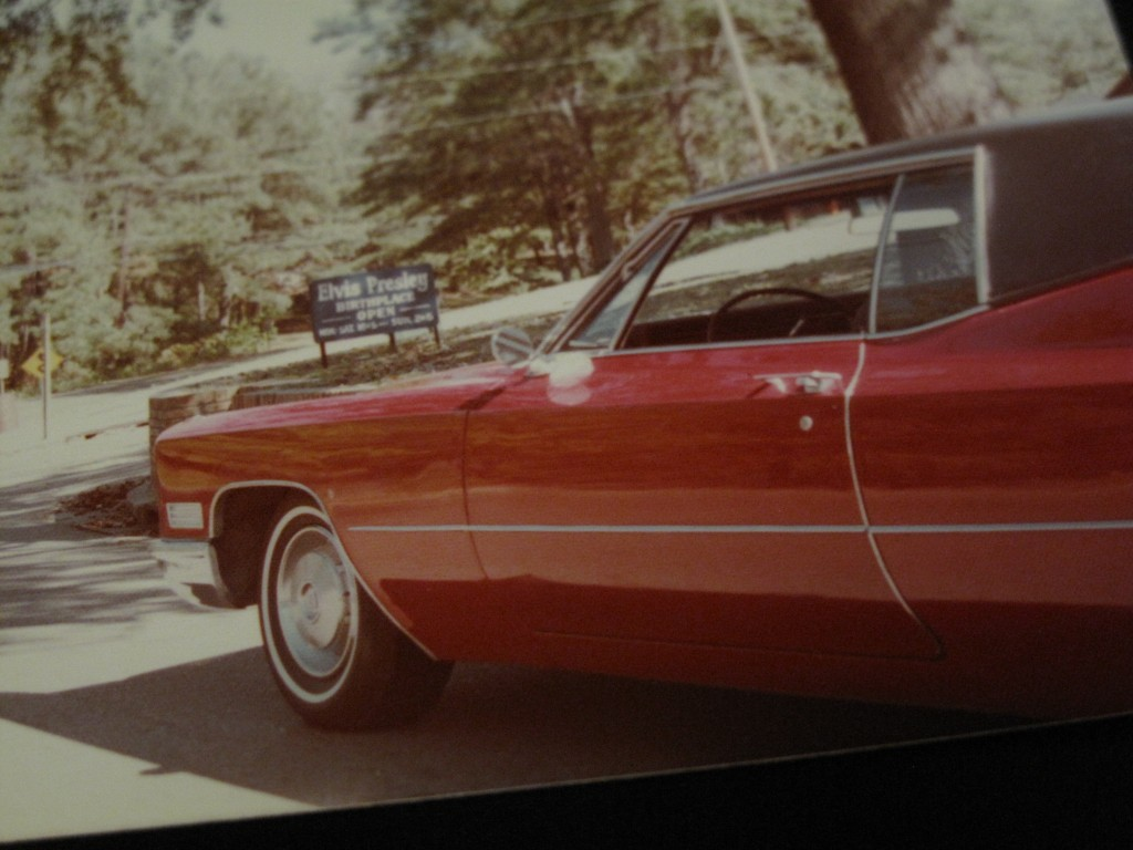 An old photo of Elvis' Coupe de Ville parked in front of the Elvis Presley Birthplace Museum. Date unknown.